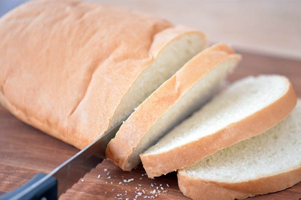 image of serrated knife cutting through bread
